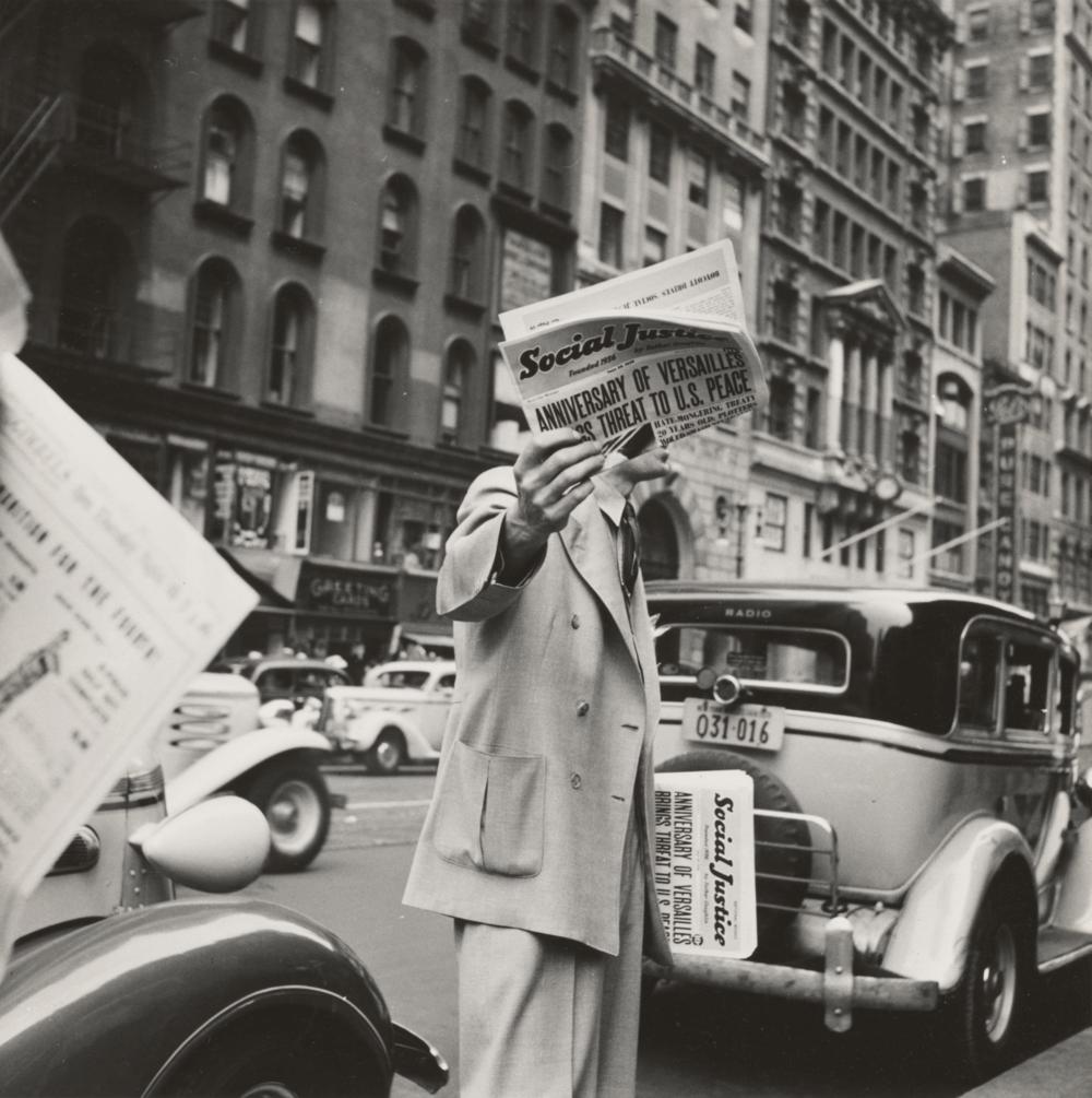 Man holding up a newspaper